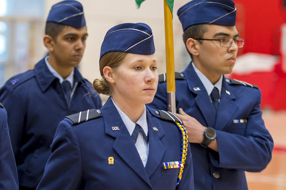 Two men and one female holding flag during Air Force ROTC ceremony.