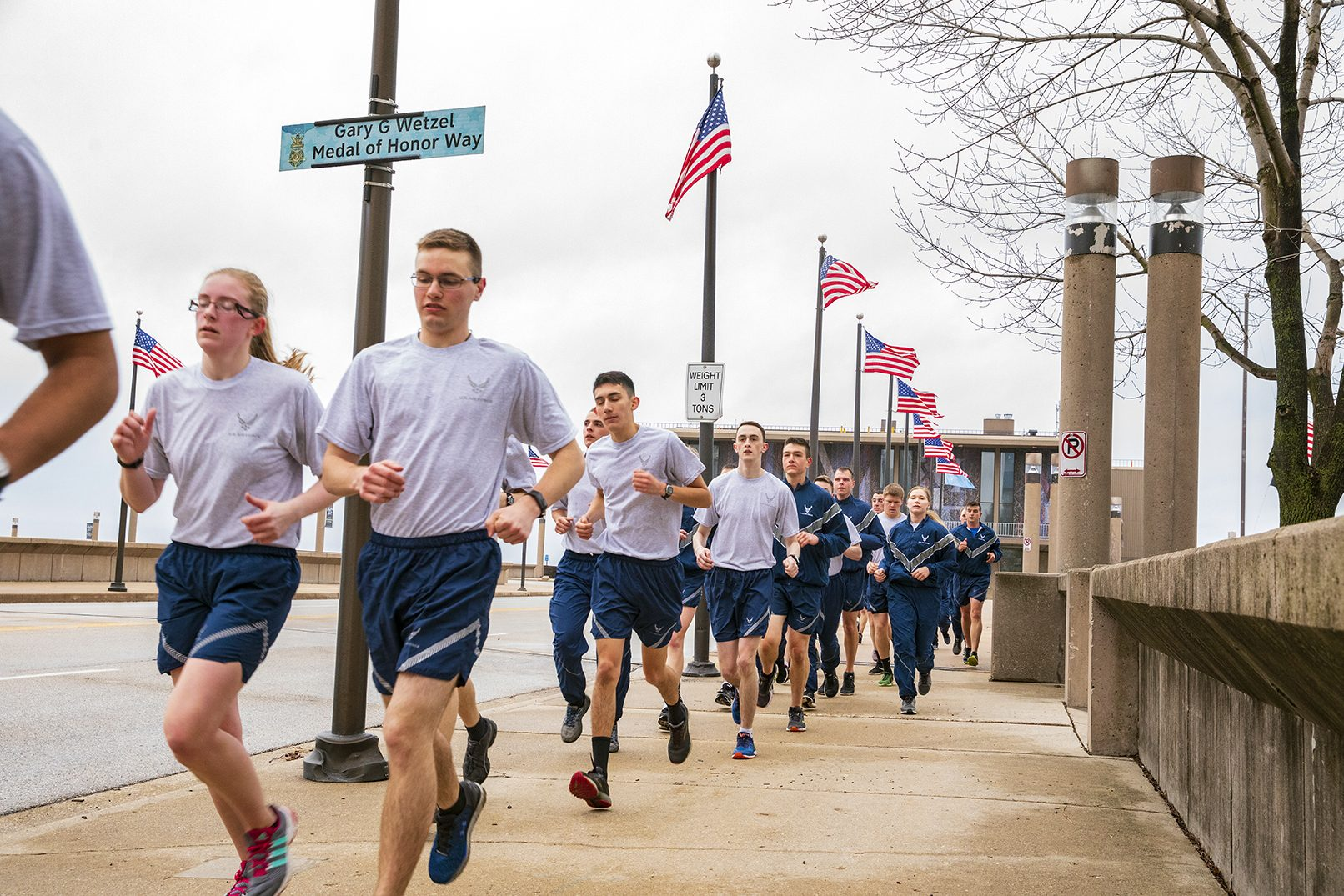 Air Force ROTC cadets running on the sidewalk beneath a line of American flags near the War Memorial in Milwaukee.