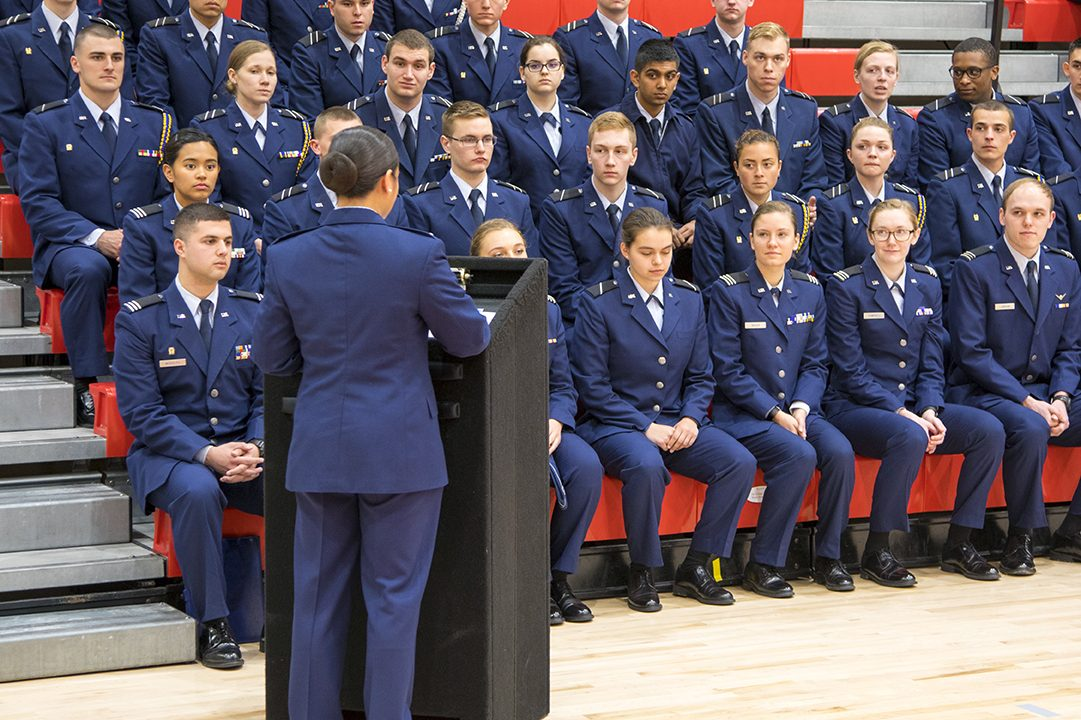 Group of Air Force ROTC cadets in blue uniforms sitting on gym bleachers during cermony.