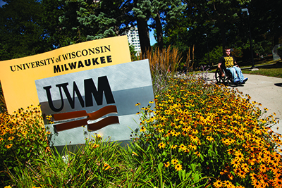 Photo - Student in a wheelchair is passing by UWM signage surrounded by flowers.