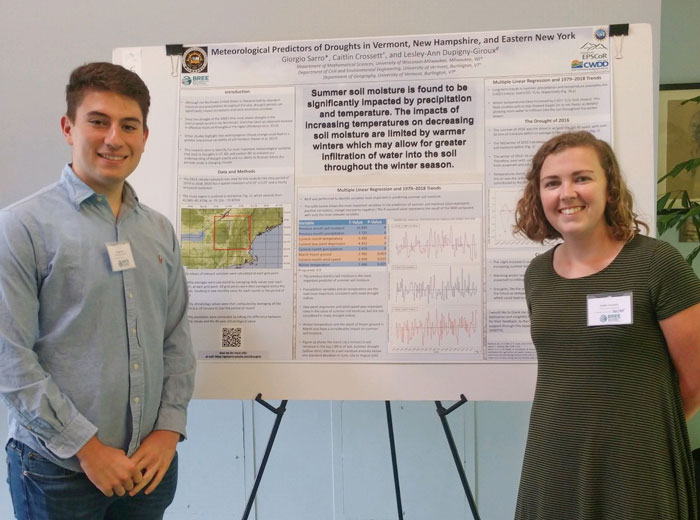 Giorgio Sarro and Caitlin Crossett in front of a poster with their research