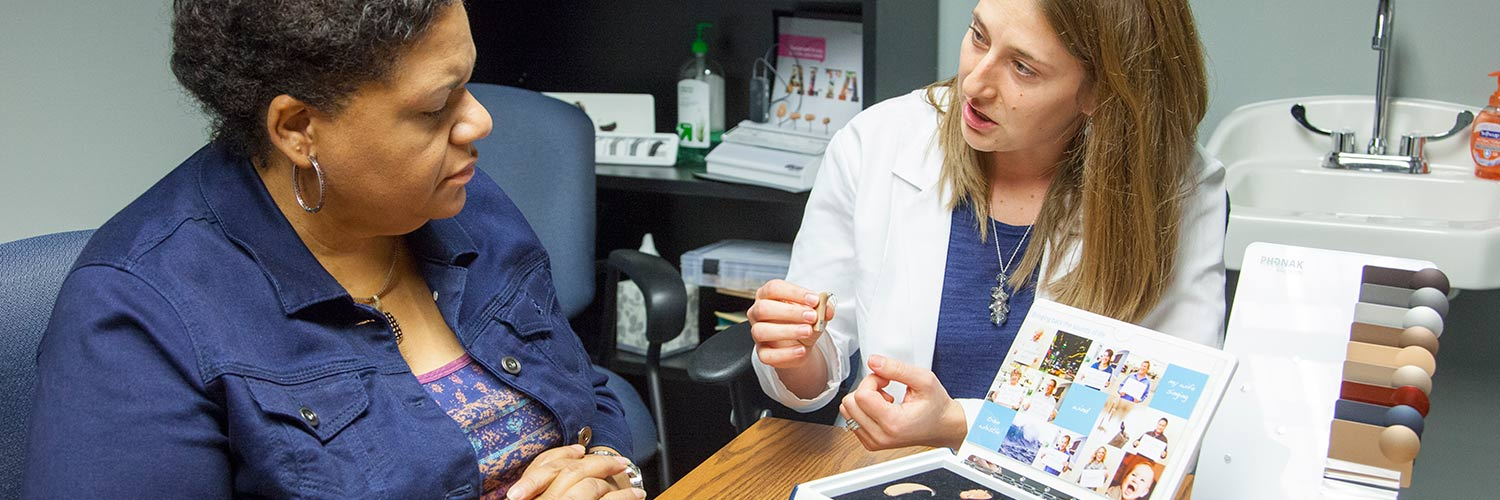 An audiologist explains to a woman the different types of hearing aids.