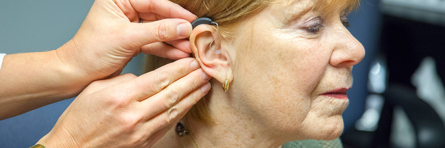 Woman having a hearing aid placed in her ear by an audiologist