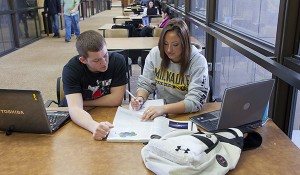 Two students study together on the library third floor bridge.