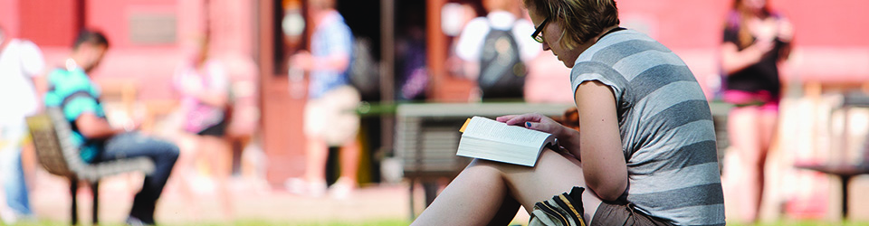 Student enjoying a book outside on the UWM campus.