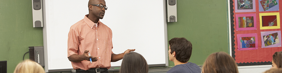 Teacher talking to the students in his class.