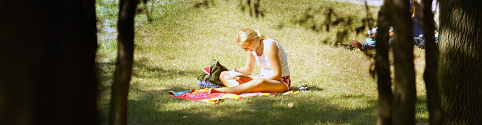 Student soaks in the sun while studying in the outdoor courtyard.