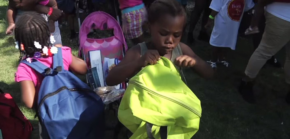 Young girl looking at her backpack during the backpack and school supply giveaway.