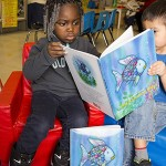 "Students at Guadalupe Head Start Center enjoy reading about ""Rainbow Fish,"" in English and Spanish."