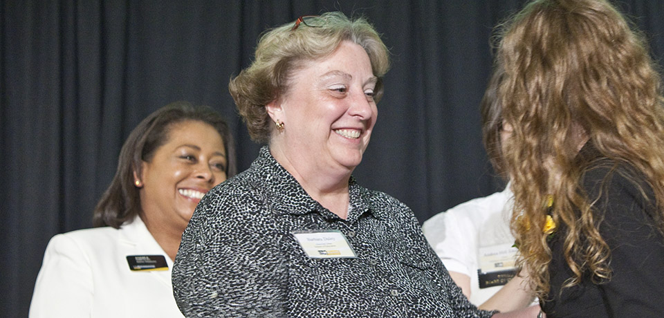 Barb Daley, School of Education, greets a student at an award ceremony.