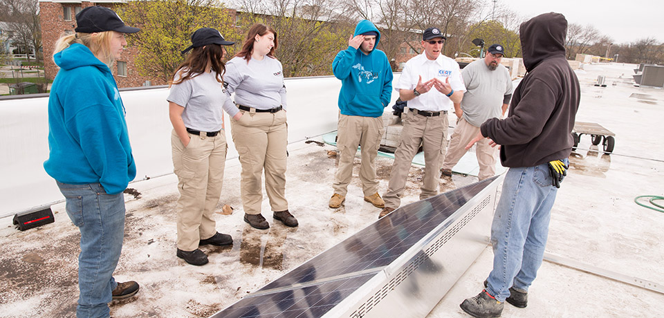 Chris Litzau (in white shirt) works with a group of his students from Racine's CERT school at a solar installation site. Litzau founded the school, which is an alternative high school designed as a hybrid career academy.