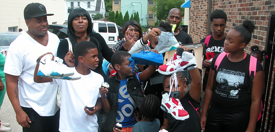 Families displaying their shoes at the Kicks for Kids 2016 event.