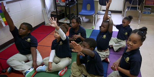 Young students at a local school raising their hands in class.