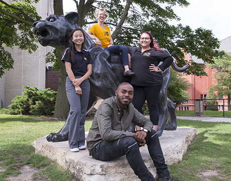 School of Education Graduate Assistants in front of Enderis Hall panther statue.