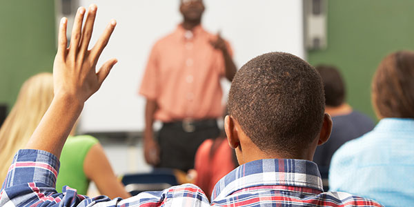 Student raising his hand during class as the teacher calls on him.