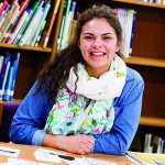 Alexandra Campos poses for a picture in her schools library.