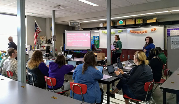 Teachers work together and listen to discussion during the College, Career and Community Ready Writers Research professional development event.