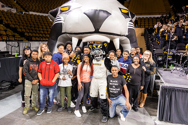 Lyndee Belanger, who earned her B.S. in elementary education in 2004, brought some special guests with her – a group of students from Milwaukee School of Excellence to cheer on the Panthers.