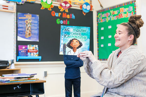Teacher displays book her students are reading in the classroom.