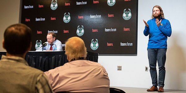 American Sign Language program alum Brice Christianson, signs during a post game interview with Milwaukee Bucks head coach Mike Budenholzer.