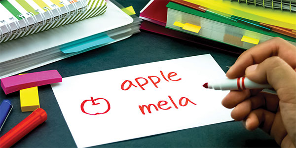 Teacher writing the word apple in different languages on a note card.