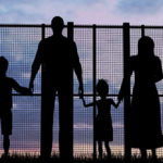 Picture of family holding hands and looking through a fence.