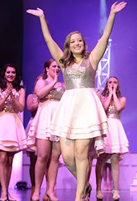 School of Education student Allison Hoffman waves to the crowd during a pageant competition.