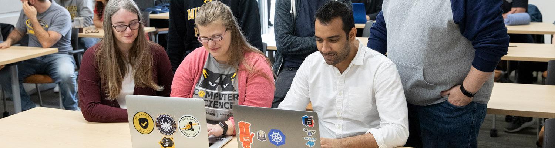 Three students looking at computers