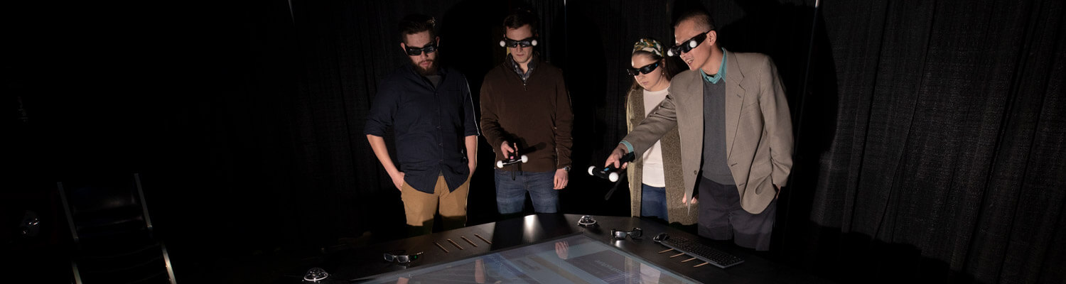 Three students and professor gather around virtual reality table