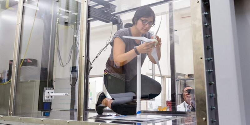 Student adjusts windmill blade in wind tunnel