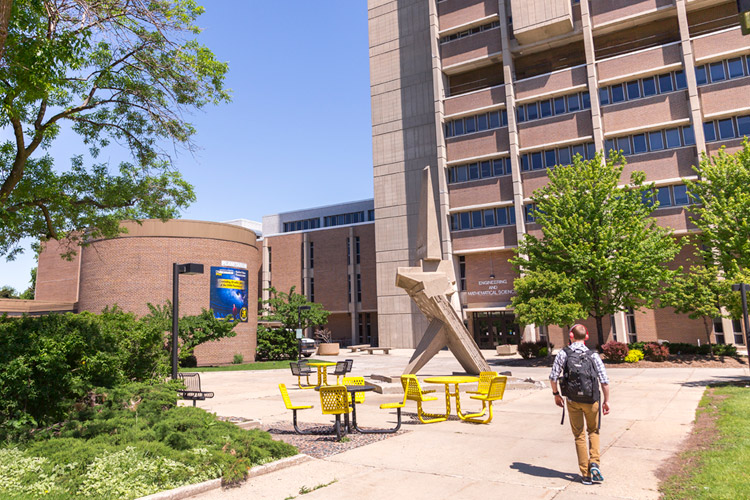 Student walking by the Engineering and Mathematical Sciences building.