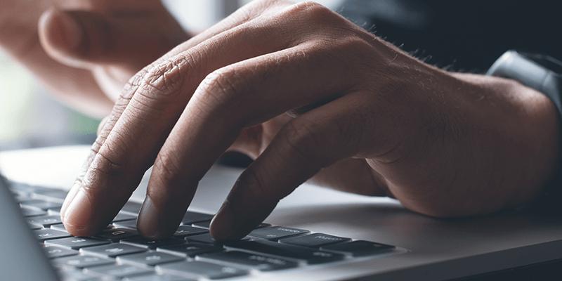 hands typing at keyboard