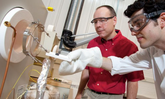 Assistant Professor Ben Church and undergraduate Daniel Kaminski load a metallic sample into a high-temperature oven.