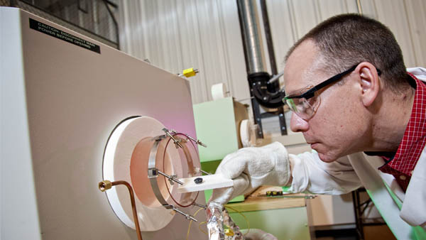 Ben Church, assistant professor of materials engineering, loads a metallic sample into a high-temperature oven.