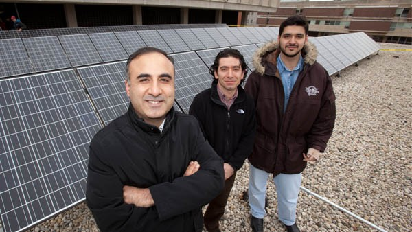 Dr. Adel Nasiri, Professor of Electrical Engineering, and grad students with solar panels on the second floor roof of Bolton Hall.