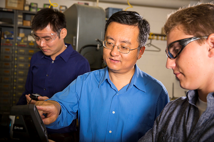 Mechanical engineering doctoral candidate Junling Xie (left) works with Associate Professor of Mechanical Engineering Chris Yuan (center) and engineering senior Jon Fisher in Wisconsin's only Industrial Assessment Center, housed at UWM.