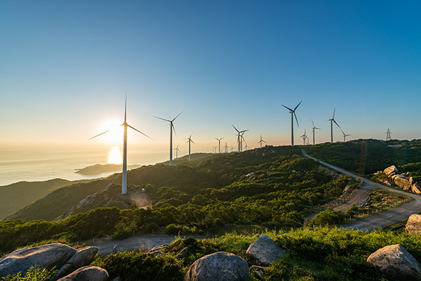 Rows of windmills on a grassy hill and the sun rising over water in the background