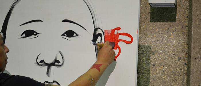 image of man's arm in front of a canvas, with a child's face in black outline, starting to paint with red