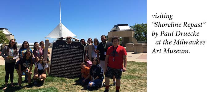 Group of native students around a sign in the ground in front of a distinct building.