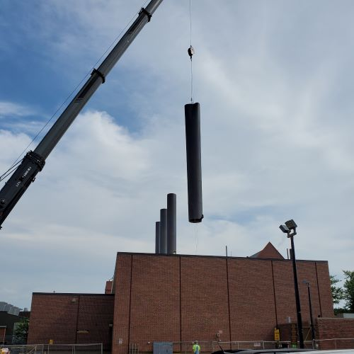 Crane swings chimney away from Heat Plant roof