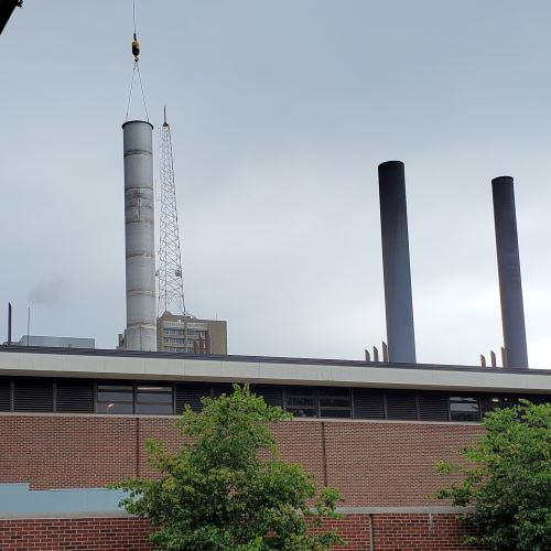 Three smokestacks in a row on the roof of a red brick building