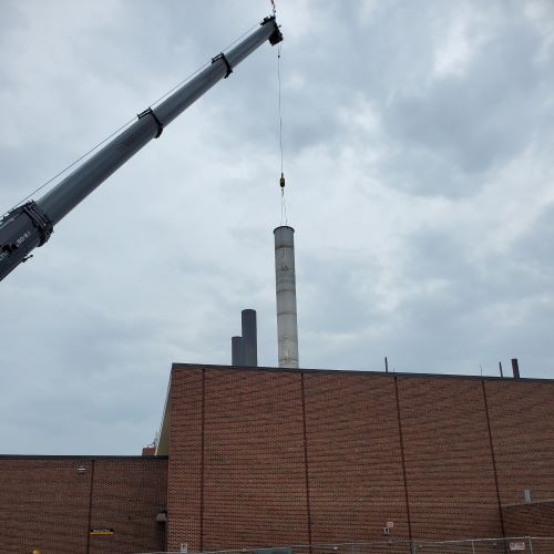 Black crane lowering gray smokestack onto the roof of a red brick building