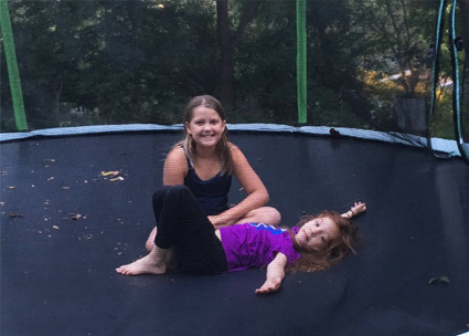 Two young girls on a trampoline