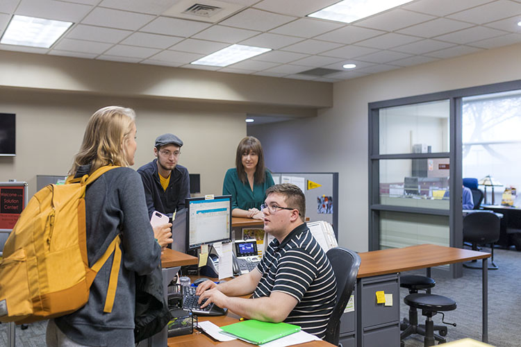 Student with backpack at desk in solution center at UWM at Waukesha. Student worker is talking to her as two staff members look on.