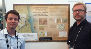 """UWM students Michael Kavalar and Jay Feiker with their poster, """"Historic Streams in Milwaukee, Wisconsin for the Integrated Regional Stormwater Management Program"""" (not pictured, Will Mobley)"""