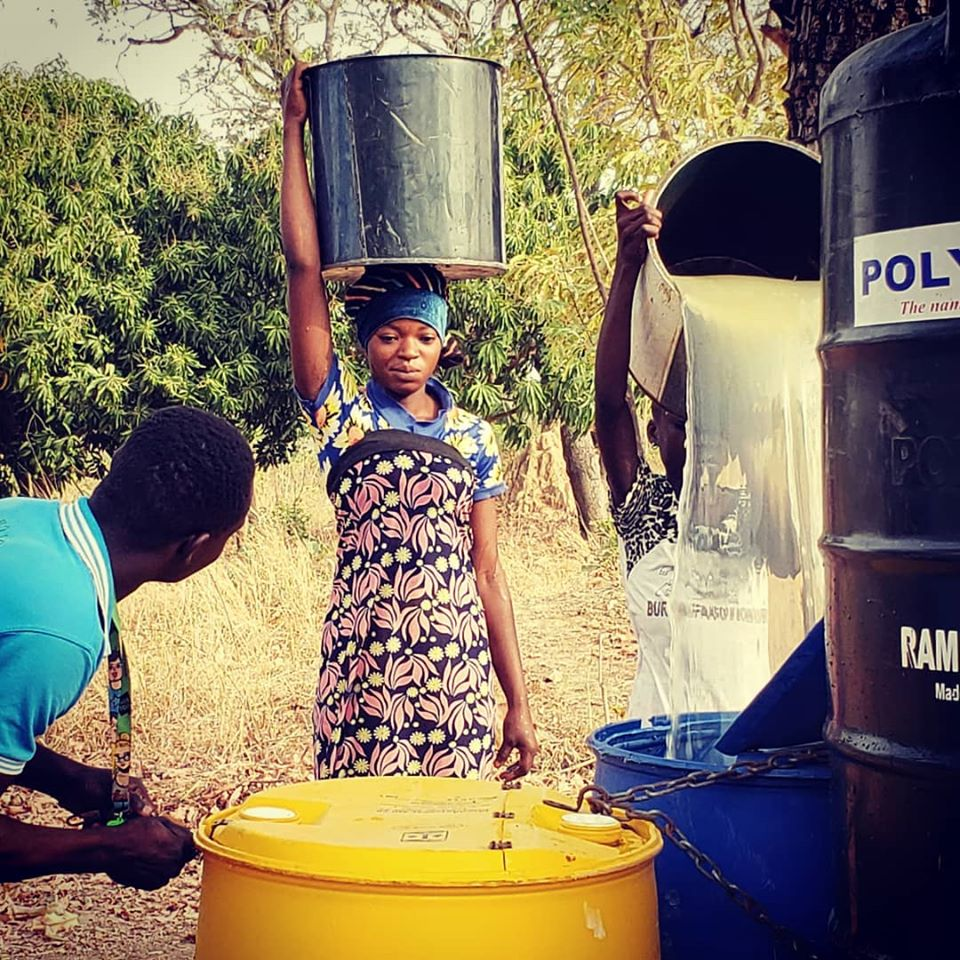 A woman in a small village in northern Ghana brings water to a filtration location.