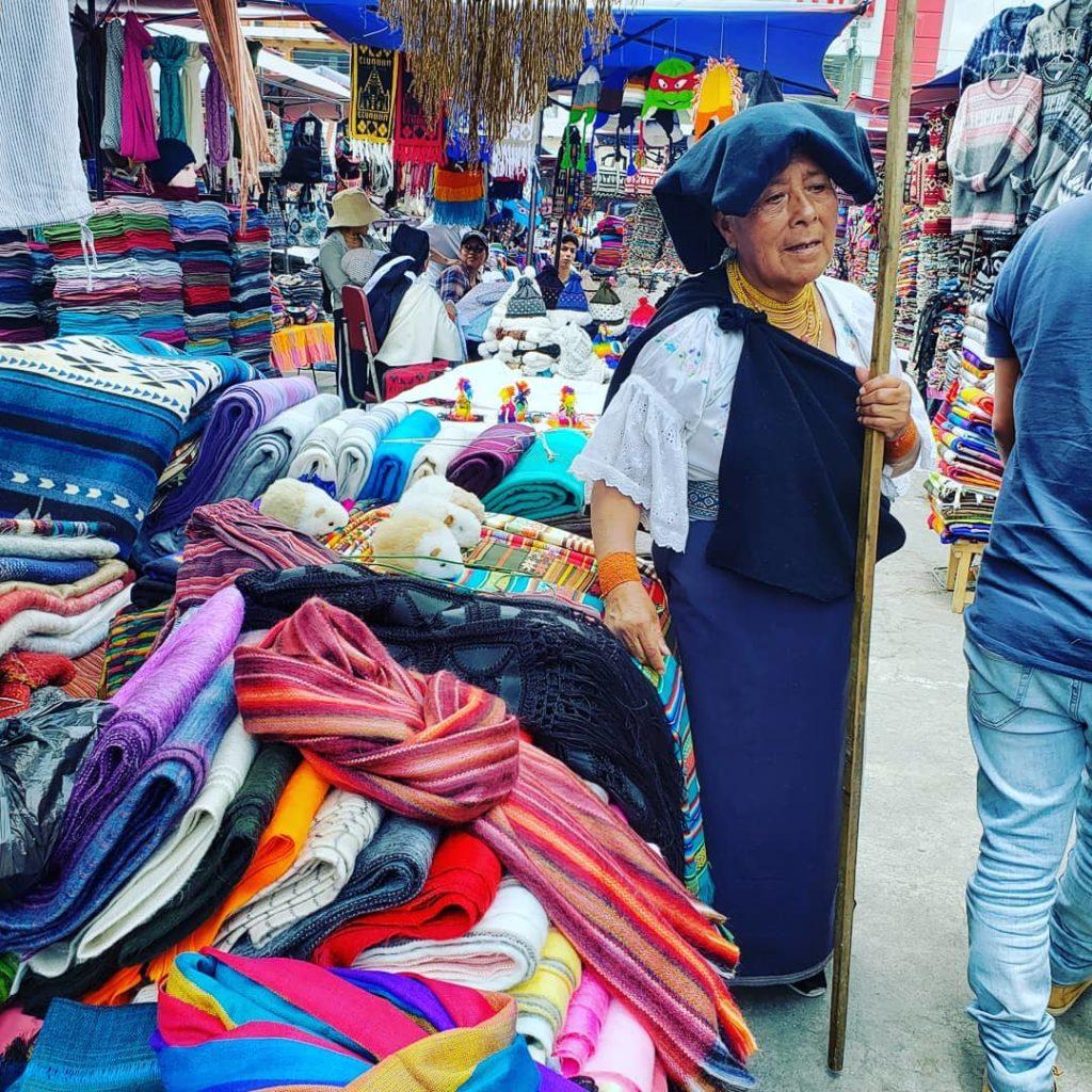 An indigenous Ecuadorian woman selling goods at the market in Otavalo, Ecuador.