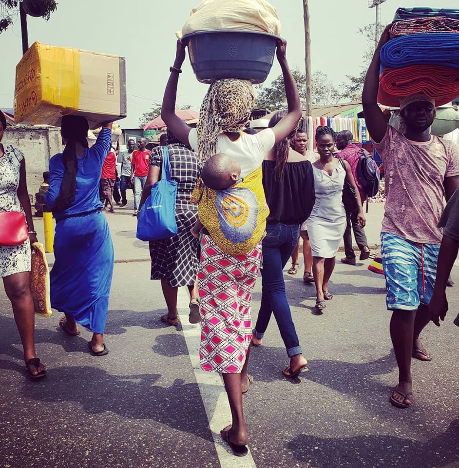 Locals crossing the street to shop and sell goods at the open air market in central Accra