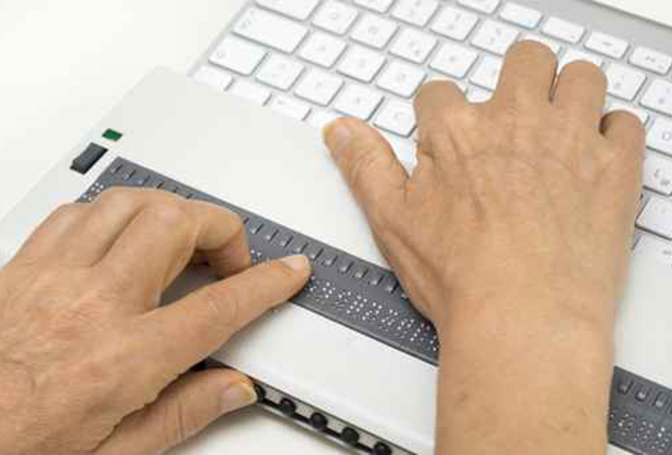 Person using a refreshable braille machine with a computer.