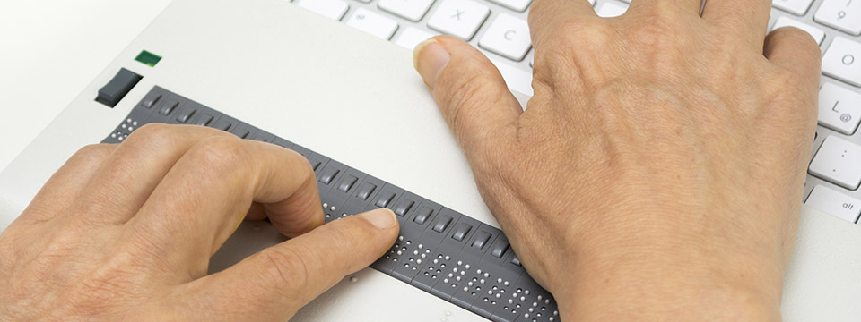 Person using a refreshable braille machine with a computer